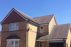 An image of a large detached house with a pitched roof, laid by AES Roofing Contractors.